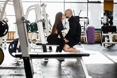Young slender pretty girl and brutal athletic man are kissing sitting together on the sport bench in the modern gym royalty free stock image