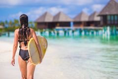 Young slender surf girl at white beach with yellow Royalty Free Stock Image