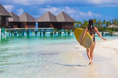 Young slender surf girl at white beach with yellow Stock Images
