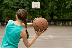 Young slender teenage girl playing basketball. Throwing the ball, view from behind royalty free stock photos