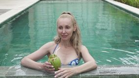 The young slender woman in bikini drinks coconut milk from a coco on the edge of the pool in the tropical resort.  stock video footage