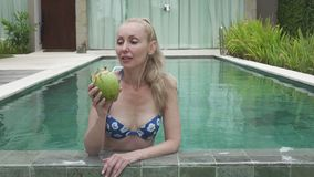 The young slender woman in bikini drinks coconut milk from a coco on the edge of the pool in the tropical resort.  stock video
