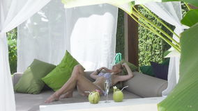 The young slender woman in bikini with a long fair hair has a rest in the tropical resort.  stock video footage