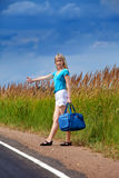 The young slender woman in a blue t-shirt and white shorts stops a passing car on the road Royalty Free Stock Images