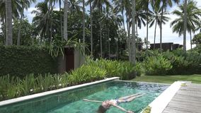 The young slender woman has a rest in the pool in the tropical resort under palm trees.  stock footage