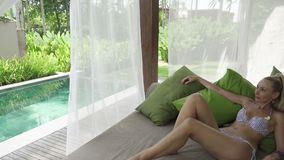The young slender woman has a rest in the tropical resort under palm trees. The young slender woman has a rest in the pool in the tropical resort under palm stock video footage
