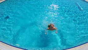 Young slender woman jumping into the pool and swimming under the water