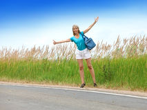 The young slender woman with a long fair hair in a blue t-shirt and white shorts stops a passing car on the road Stock Image