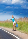 The young slender woman with a long fair hair stops a passing car on the road Stock Image