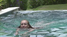 The young slender woman with long hair in Bikin swims in the pool under palm trees in the tropical resort.  stock footage