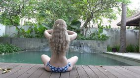 The young slender woman with long hair meditates on the edge of the pool in the tropical resort.  stock footage