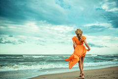 A young slender woman in orange dress is walking barefoot towards the storming sea. The train of her dress is waving. Cool wind in her hair.Outdoor shot. Copy Royalty Free Stock Photography