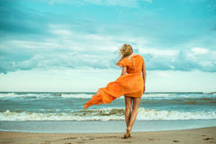 A young slender woman in orange dress is walking barefoot towards the storming sea Stock Photo