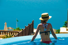 Young slender woman in pool enjoy vacation and looking at Dead Sea. View from behind. 2017 New Travel season concept. Copyspace. Stock Photography