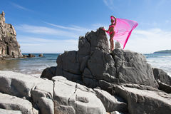 Young slender woman on the sea rocky shore in a pink swimming suit and a pink fabric fluttering in the wind. Stock Photos