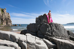 Young slender woman on the sea rocky shore in a pink swimming suit and a pink fabric fluttering in the wind. Royalty Free Stock Image
