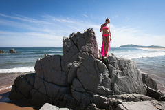 Young slender woman on the sea rocky shore in a pink swimming suit and a pink fabric fluttering in the wind. Stock Image