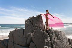 Young slender woman on the sea rocky shore in a pink swimming suit and a pink fabric fluttering in the wind. Royalty Free Stock Images