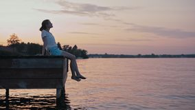 Young Slender Woman is Sitting above Water at Summer Sunset Glow and Relaxing. Amazing background for your motto stock video footage