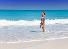 The young slender woman in white bikini goes to bathe in waves Sea Royalty Free Stock Photography