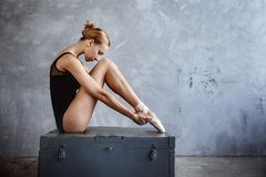 Young ballerina in a black dancing suit is posing in a loft studio. Young slim ballerina in a black dancing suit is posing in a loft studio Stock Images