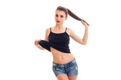 Young slim beautiful girl in t-shirt and shorts holding hand tail and posing for the camera Royalty Free Stock Photos