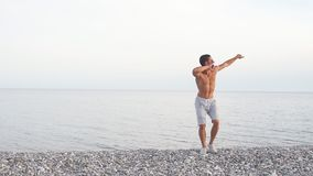 Young slim beautiful male on beach, dancing, summer vacation, having fun, positive mood. Young slim beautiful male on beach, playful, dancing, summer vacation stock footage