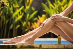 Young slim beautiful woman in bikini applying oil Stock Image