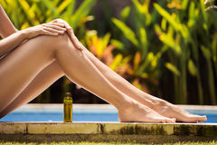 Young slim beautiful woman in bikini applying oil Stock Photo