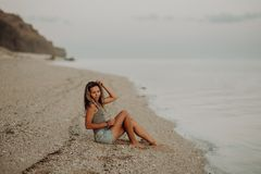 Young slim beautiful woman girl on sunset beach, indie style. Rock background stock image