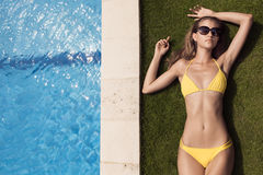 Young slim beautiful woman in yellow bikini sunbathing Stock Images