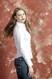 Young slim beautiful young blond woman with long legs and hair in Bedlam shirt and jeans Stock Photos