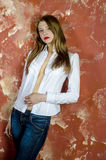 Young slim beautiful young blond woman with long legs and hair in Bedlam shirt and jeans Royalty Free Stock Image