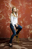 Young slim beautiful young blond woman with long legs and hair in Bedlam shirt and jeans Stock Image