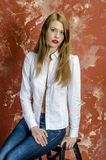 Young slim beautiful young blond woman with long legs and hair in Bedlam shirt and jeans Royalty Free Stock Photography