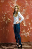 Young slim beautiful young blond woman with long legs and hair in Bedlam shirt and jeans Royalty Free Stock Photo