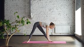 Young slim blond girl is doing yoga complex in studio with white walls. She is starting with warrior poses, then bending. Young slim blond girl is doing yoga stock footage