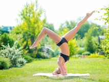 Young slim blond woman making yoga exercises. Girl is standing o. N her head pose. Healthy lifestyle and fitness. Stretching outdoors Stock Photography