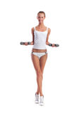 A young and slim blond woman in white lingerie doing fitness Royalty Free Stock Photos