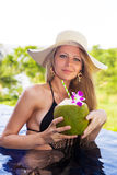 Young slim blonde woman hat drinks healthy coconut juice Royalty Free Stock Photography