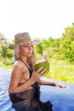Young slim blonde woman hat drinks healthy detox coconut juice Royalty Free Stock Photo