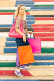 Young slim blonde woman holding shopping bags stands on the stairs. And looking aside Stock Photo