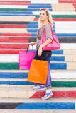 Young slim blonde woman holding shopping bags stands on the stairs Stock Images