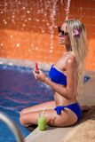 Young slim blonde woman with long hair in sunglasses eat watermelon and drinks guava juice suntan near swimming pool. Young slim blonde woman with long hair in royalty free stock photography
