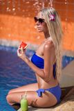 Young slim blonde woman with long hair in sunglasses eat watermelon and drinks guava juice suntan near swimming pool. Young slim blonde woman with long hair in royalty free stock images