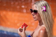 Young slim blonde woman with long hair in sunglasses eat watermelon and suntan near swimming pool. Young slim blonde woman with long hair in sunglasses eat royalty free stock images