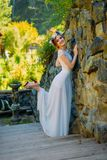 A young sexy bride with circlet of flowers posing and smiling standing on wooden stairs near rock fence stock images