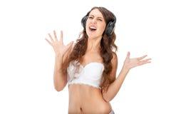Young slim brunette girl listen music in headphones Royalty Free Stock Image