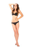 Young slim brunette girl posing in a studio in lacy underwear Stock Photo