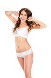 Young slim brunette girl posing in a studio in lacy underwear Royalty Free Stock Photography